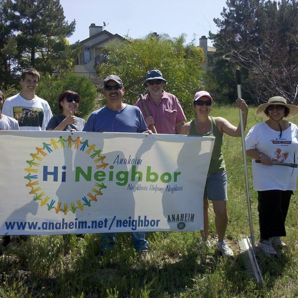 "Group of gardeners standing in the original garden site, holding a ""Hi Neighbor"" banner"